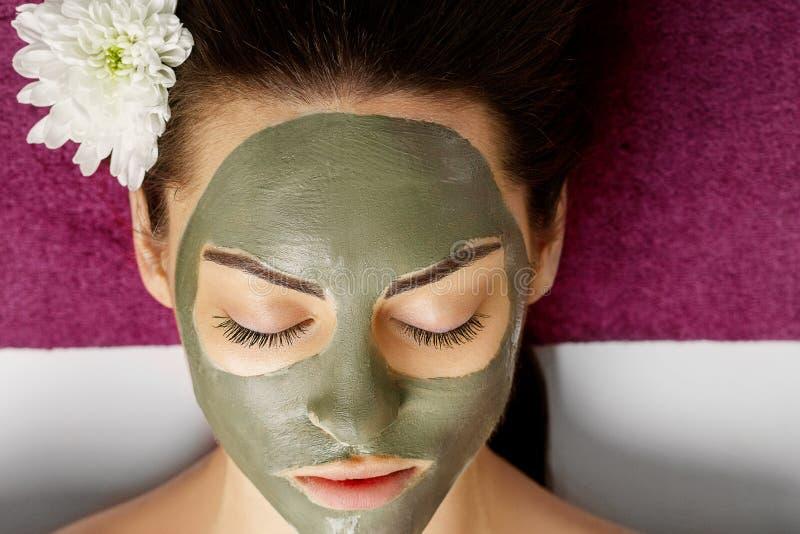 Mulher com m?scara facial da argila em termas da beleza Skincare Conceito da beleza Tratamento facial cosmetology O corpo importa imagens de stock royalty free