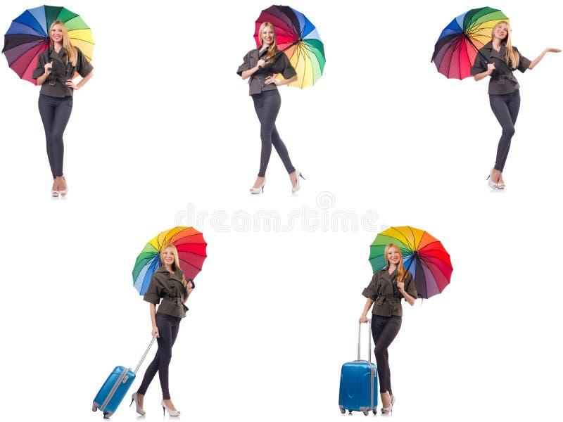 A mulher com a mala de viagem e o guarda-chuva isolados no branco foto de stock