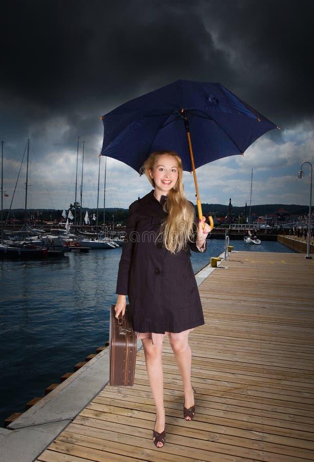 Mulher com mala de viagem e o guarda-chuva velhos no porto imagem de stock