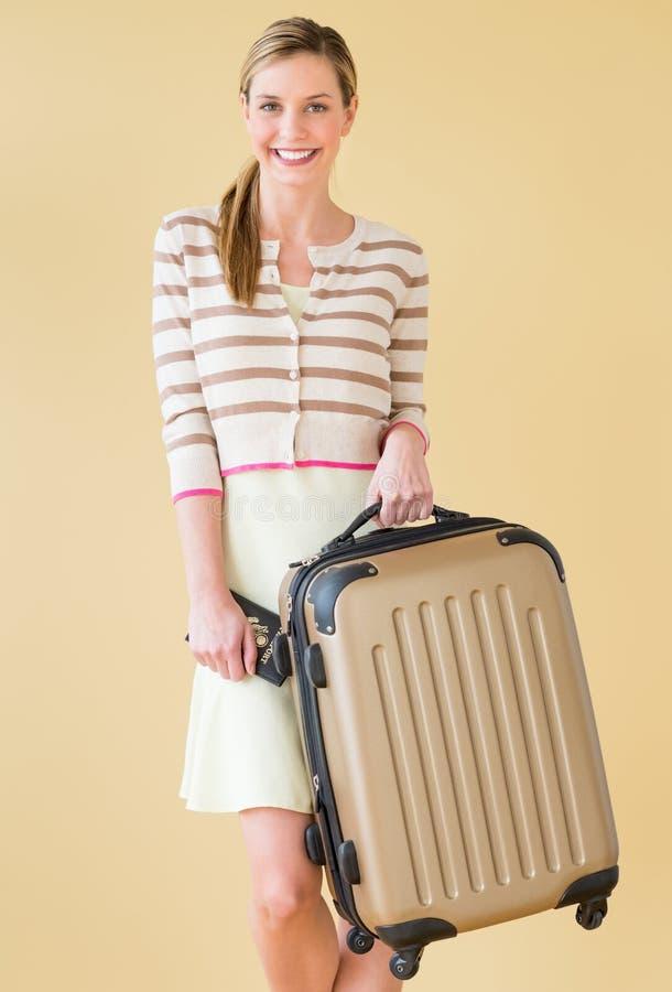 Mulher com mala de viagem e passaporte que está contra Backgr colorido fotos de stock royalty free