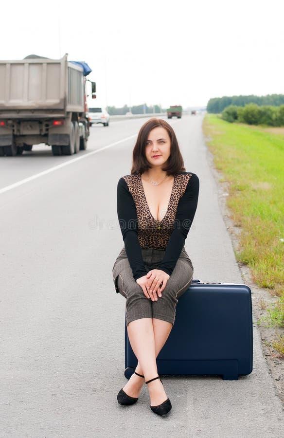 Mulher com a mala de viagem na estrada imagem de stock royalty free