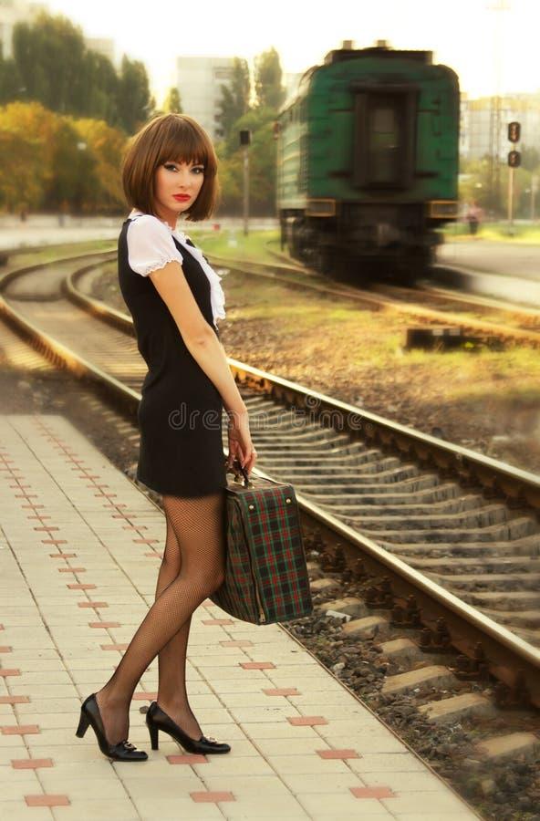 Mulher com a mala de viagem na plataforma foto de stock