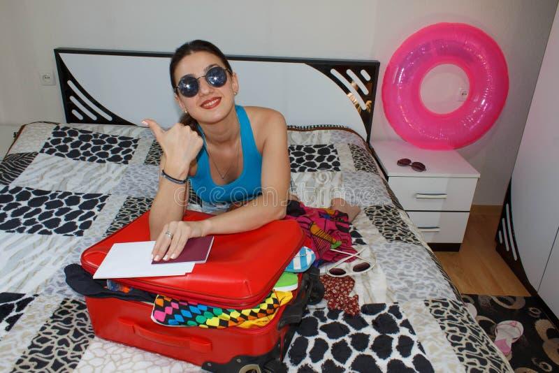 Mulher com a mala de viagem que senta-se na cama no hotel A menina bonita com uma mala de viagem do vermelho ama viajar fotografia de stock royalty free