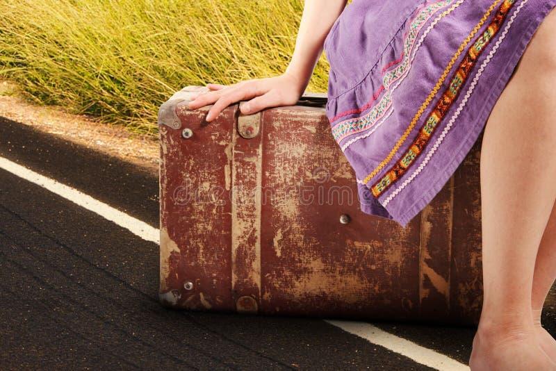 Mulher com a mala de viagem velha do vintage na estrada foto de stock royalty free