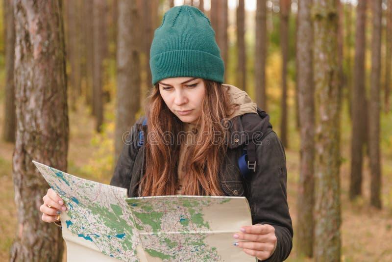 Mulher com mapa do curso e trouxa na floresta do pinho fotografia de stock royalty free