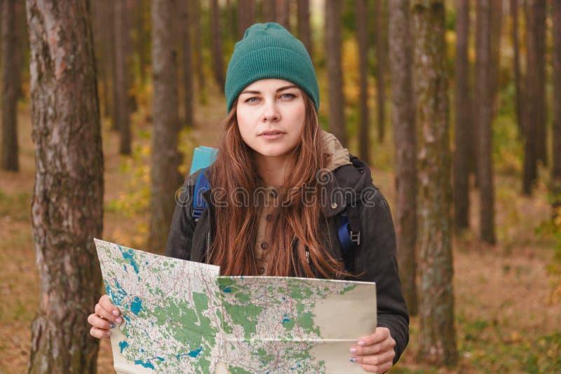 Mulher com mapa do curso e trouxa na floresta do pinho foto de stock