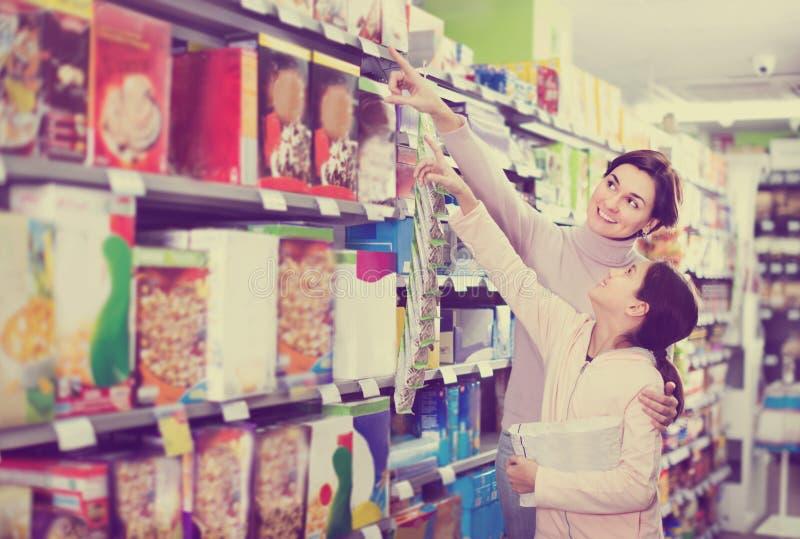Mulher com a menina que procura o cereal de café da manhã fotografia de stock