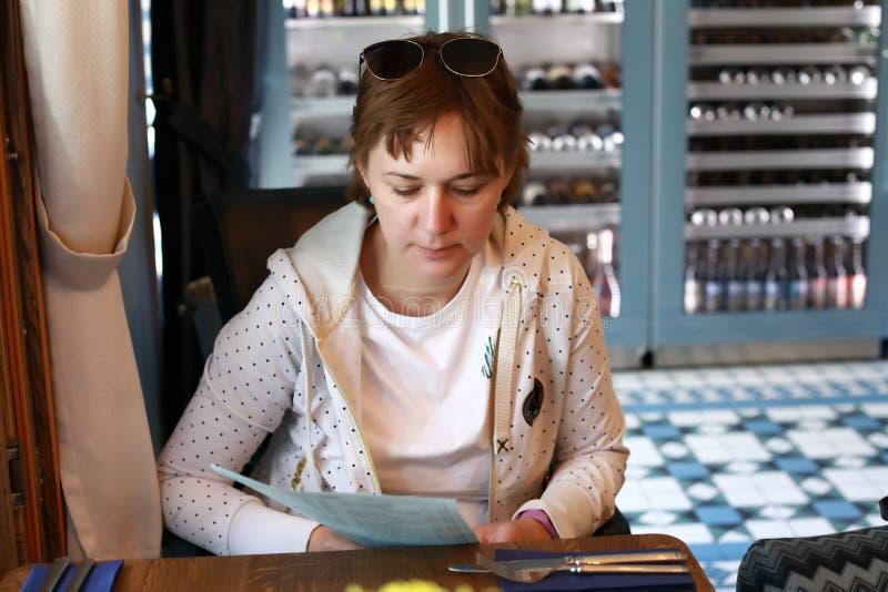 Mulher com menu no restaurante foto de stock