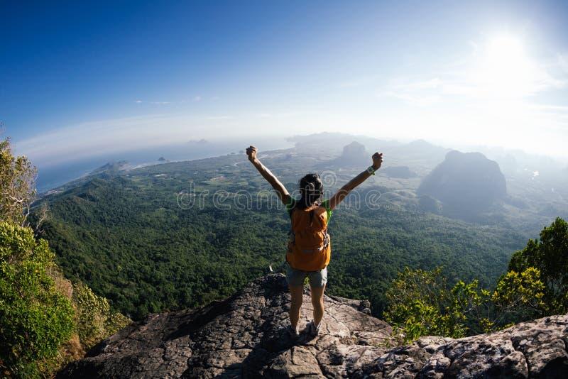 A mulher com mochileiro aprecia a vista na parte superior da montanha imagem de stock