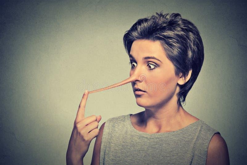Mulher com nariz longo Conceito do mentiroso fotografia de stock