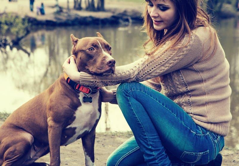 Mulher com a natureza do cão que joga junto fotografia de stock royalty free
