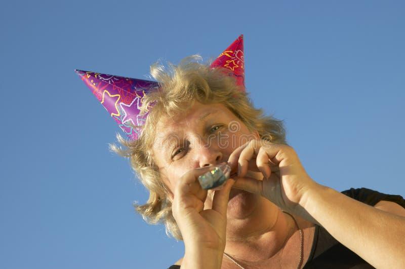 Mulher com noise-maker imagens de stock royalty free