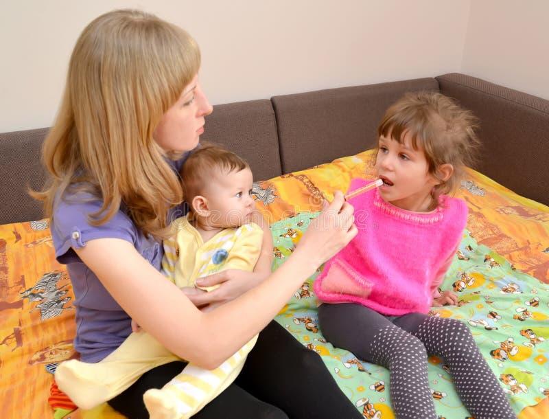 A mulher com o bebê nas mãos dá à medicina doente da menina por meio do batcher tratamento fotos de stock
