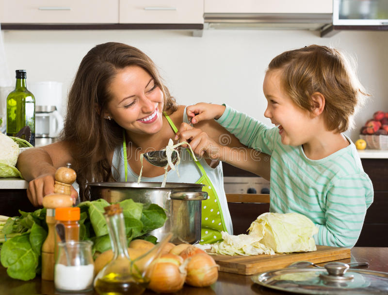 Mulher com o bebê que cozinha na cozinha foto de stock