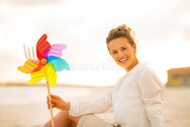 Mulher com o brinquedo colorido do moinho de vento que senta-se na praia imagens de stock royalty free