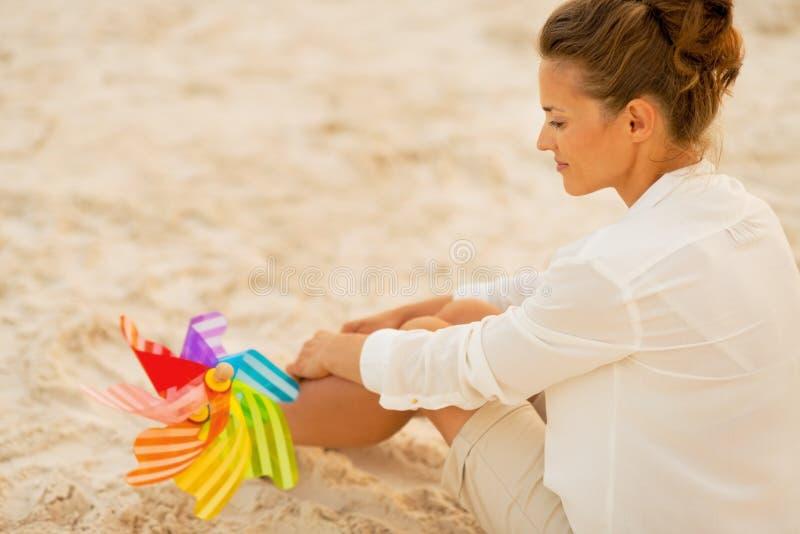 Mulher com o brinquedo colorido do moinho de vento que senta-se na praia imagens de stock