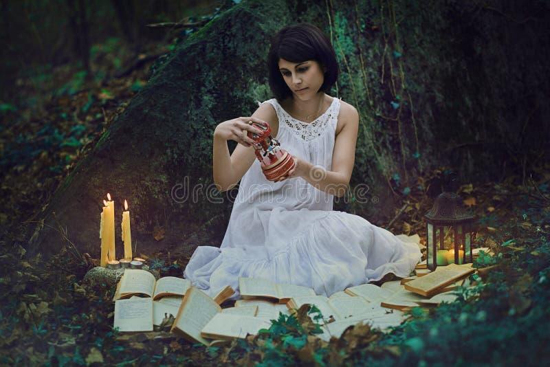 Mulher com o brinquedo do vintage na floresta escura imagens de stock royalty free