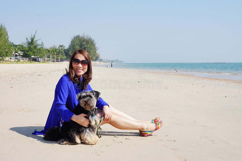 Mulher com o cão pequeno na praia foto de stock