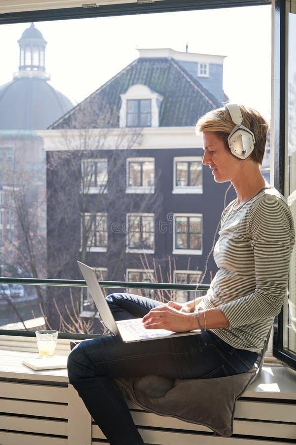 Mulher com o cabelo curto que senta-se perto da janela aberta no peitoril com opinião do canal com portátil e que escuta a música foto de stock