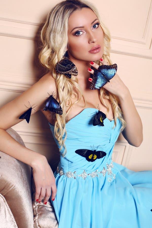 Mulher com o cabelo louro longo que veste o vestido azul elegante, levantando com muitas borboletas imagens de stock