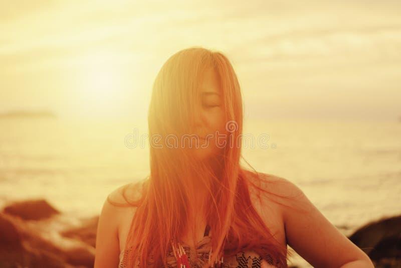 Mulher com o cabelo que flui abaixo de sua cara na praia no por do sol imagem de stock royalty free