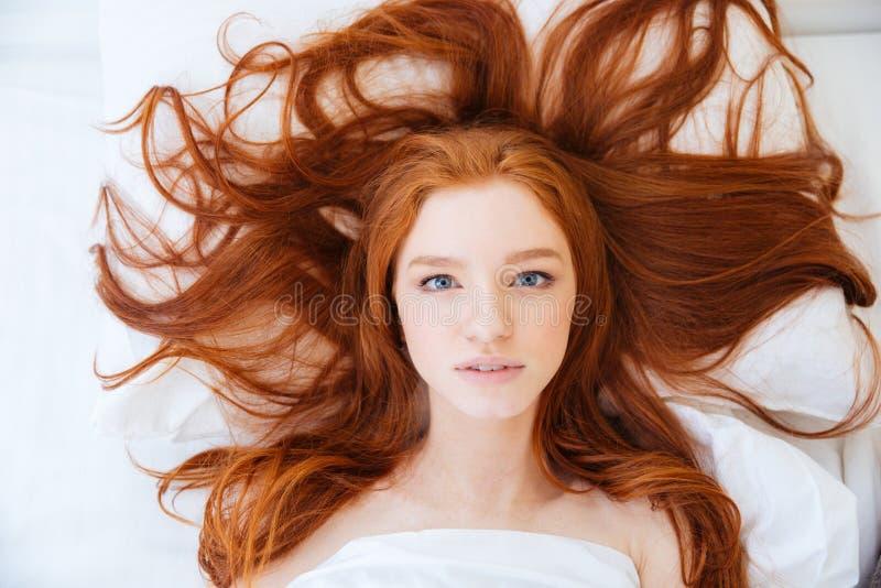 Mulher com o cabelo vermelho longo bonito que encontra-se na cama fotos de stock royalty free