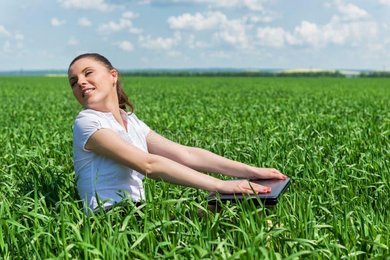 Mulher com o caderno no campo verde foto de stock