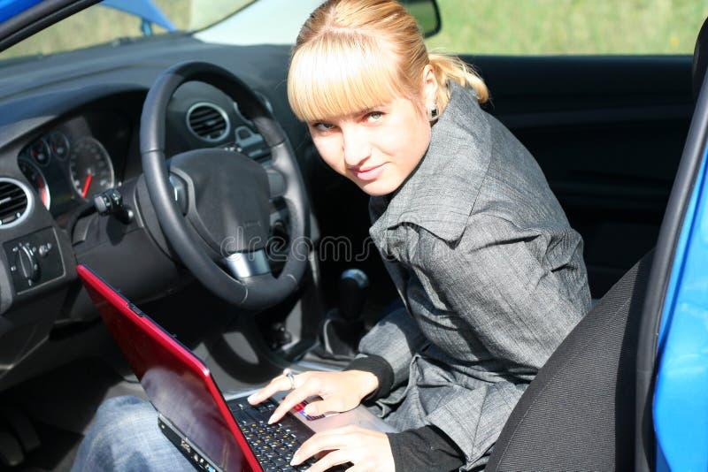 Mulher com o caderno no carro fotografia de stock
