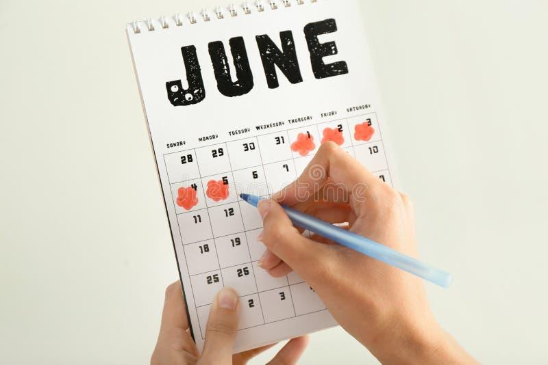 Mulher com o calendário menstrual no fundo claro fotografia de stock royalty free