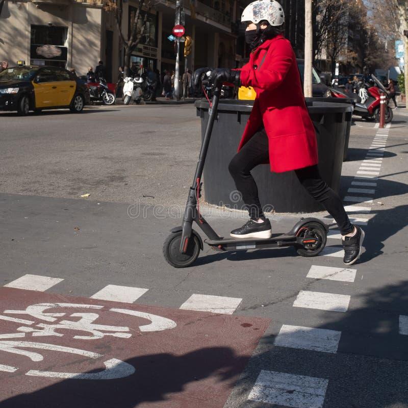 Mulher com o capacete no 'trotinette' elétrico do impulso que comuta em Barcelona central imagens de stock royalty free