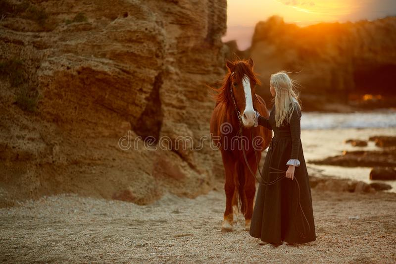 Mulher com o cavalo no litoral rochoso fotos de stock royalty free