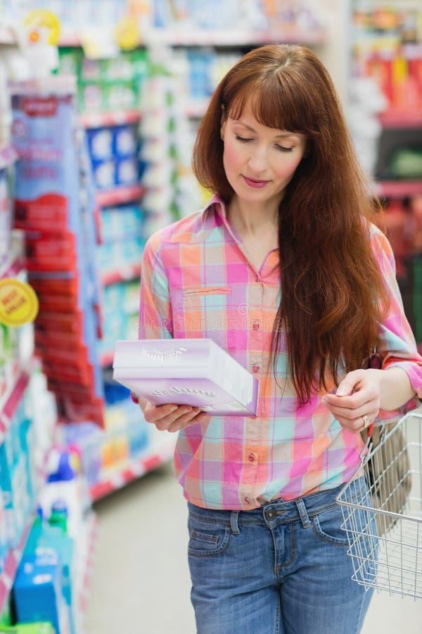 Mulher com o cesto de compras que guarda o produto fotos de stock royalty free