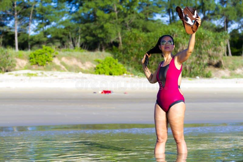 Mulher com o chapéu carmesim da mostra do biquini na proibição Krut da praia imagem de stock royalty free