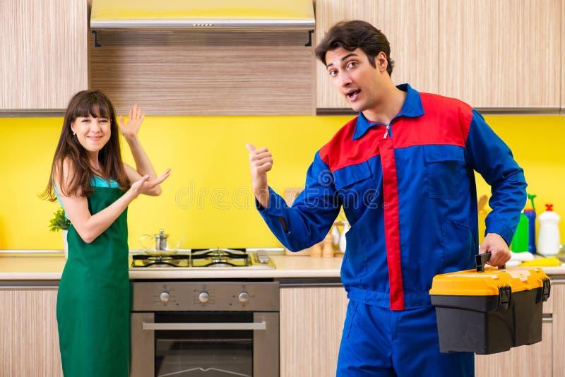 A mulher com o contratante na cozinha que discute o reparo fotos de stock