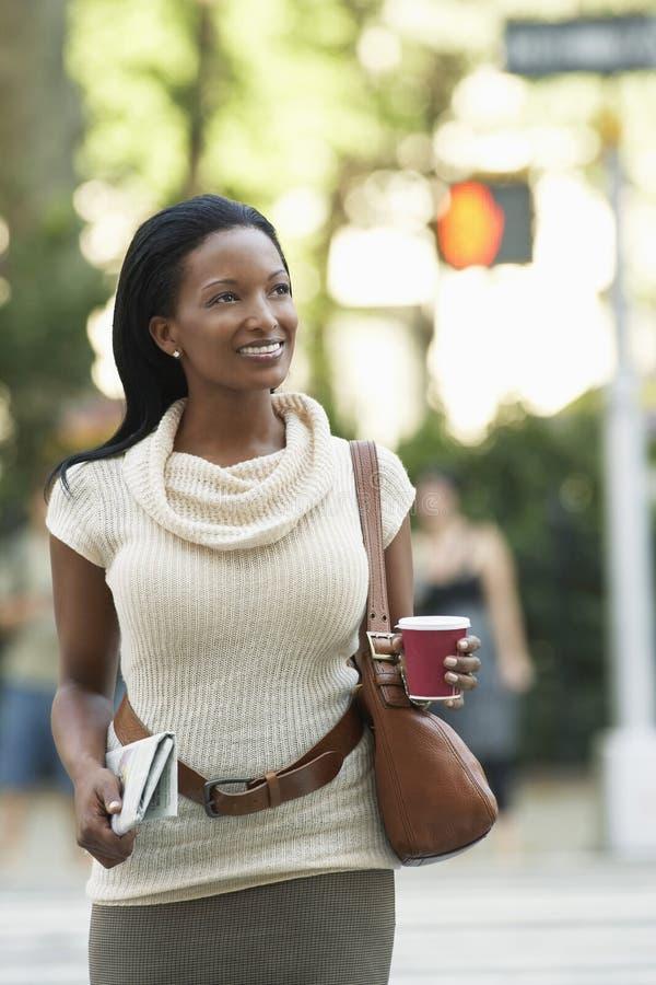 Mulher com o copo do jornal e de café na rua imagens de stock