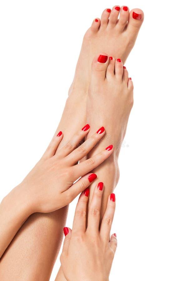 Mulher com o dedo e as unhas do pé vermelhos bonitos imagem de stock