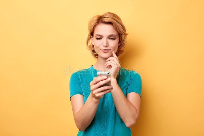 Mulher com o dedo em seu mordente que olha a tela de seu smartphone fotos de stock royalty free