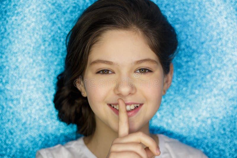 Mulher com o dedo na boca que mostra o sinal do silêncio isolado no fundo branco E imagens de stock