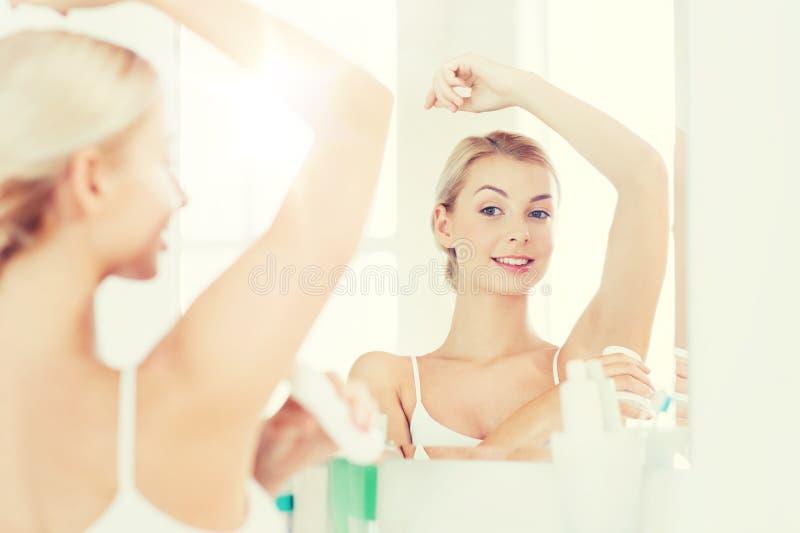 Mulher com o desodorizante antiperspirante no banheiro foto de stock