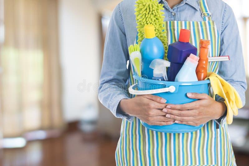 Mulher com o equipamento da limpeza pronto para limpar a casa foto de stock