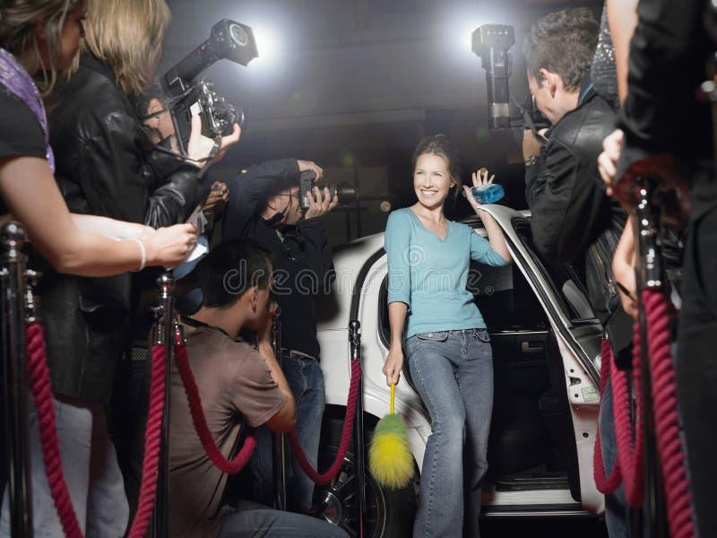 Mulher com o equipamento da limpeza que levanta em Front Of Paparazzi foto de stock