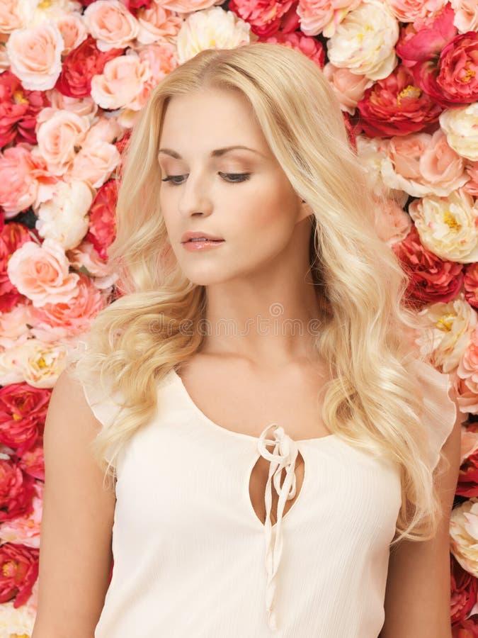 Mulher com o fundo completo das rosas foto de stock royalty free