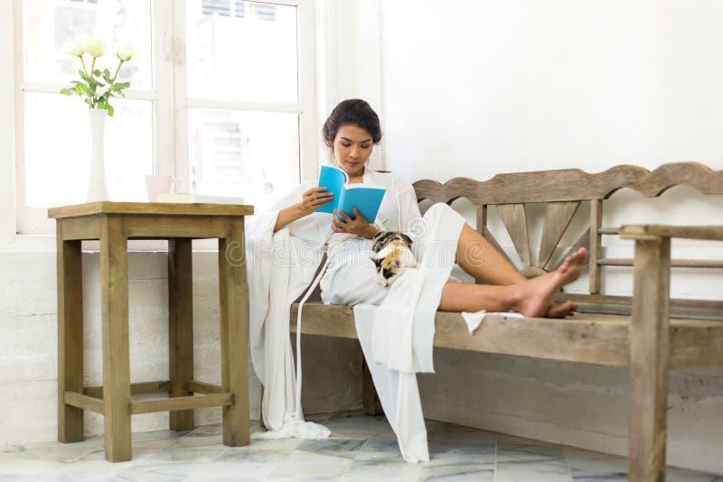 Mulher com o gato que relaxa pela janela no livro de leitura de madeira do sofá fotografia de stock
