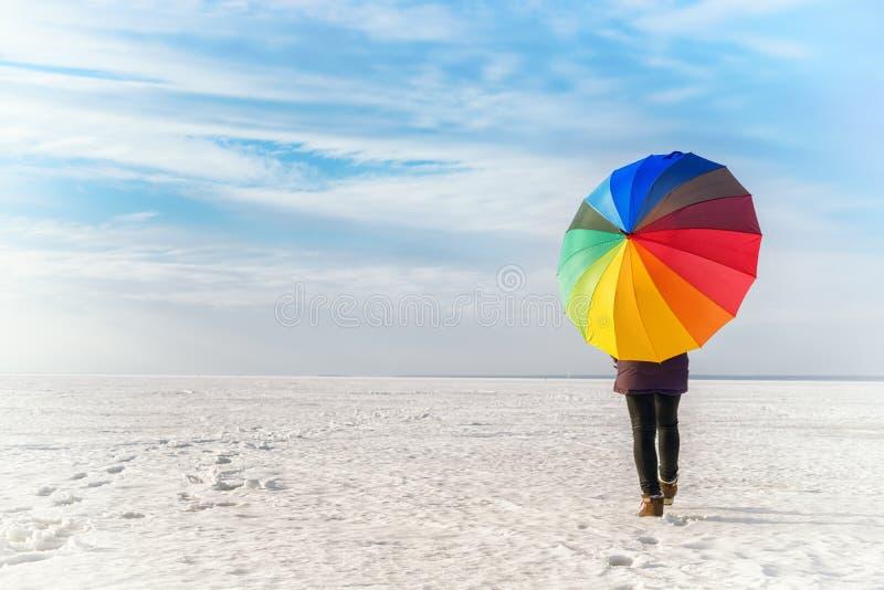 Mulher com o guarda-chuva colorido arco-íris que anda no mar congelado fotografia de stock