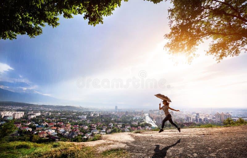 Mulher com o guarda-chuva que salta sobre a arquitetura da cidade no por do sol imagens de stock royalty free
