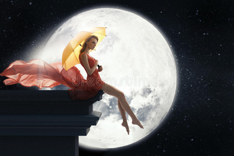 Mulher com o guarda-chuva sobre o fundo da Lua cheia