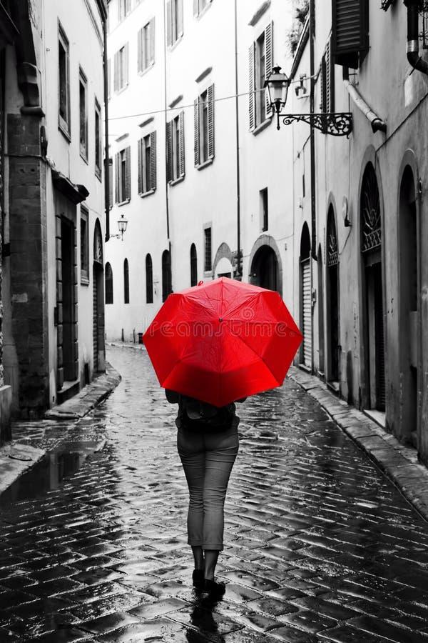Mulher com o guarda-chuva vermelho na rua retro na cidade velha Vento e chuva fotografia de stock