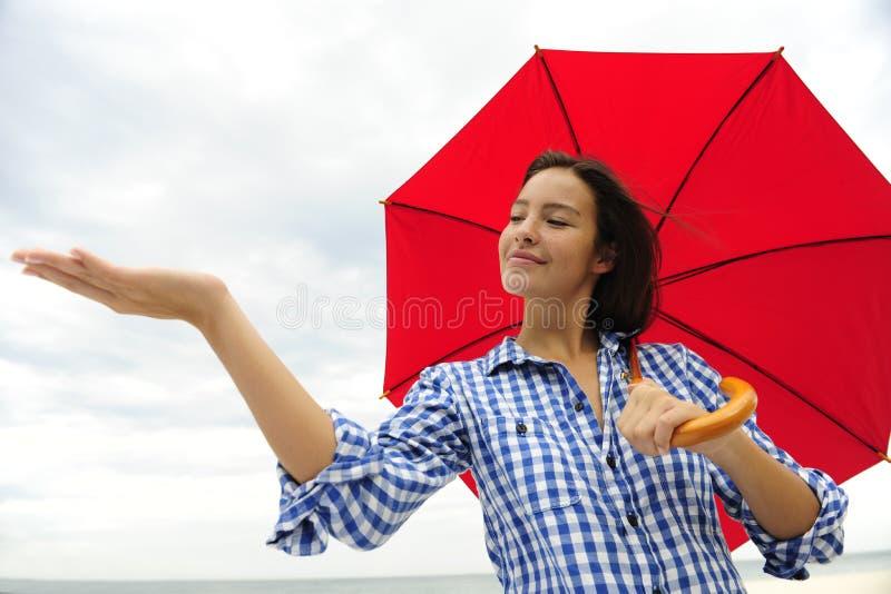 Mulher com o guarda-chuva vermelho que toca na chuva fotos de stock royalty free