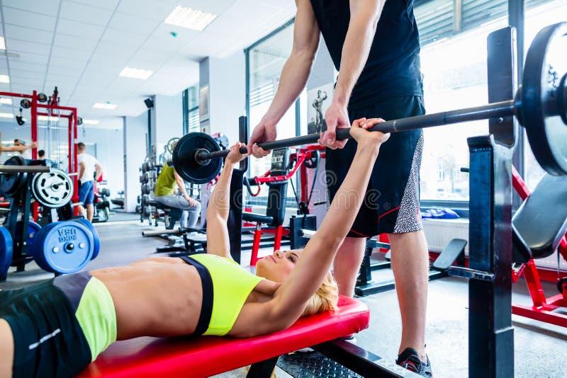 Mulher com o instrutor pessoal na imprensa de banco no gym foto de stock