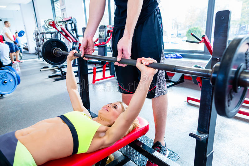 Mulher com o instrutor pessoal na imprensa de banco no gym foto de stock royalty free